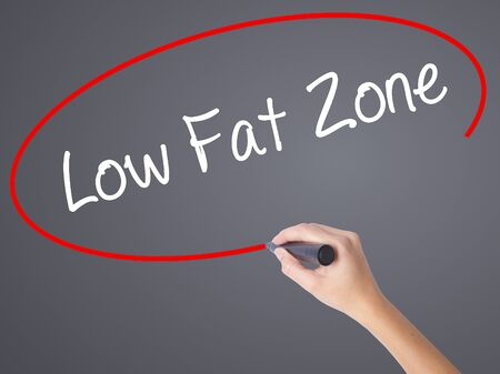 lowering: Woman Hand Writing Low Fat Zone with black marker on visual screen. Isolated on grey. Business concept. Stock Photo