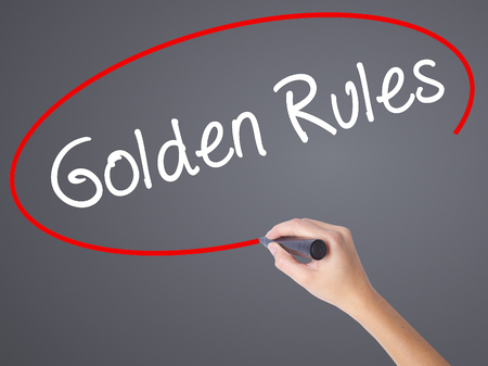 respectful: Woman Hand Writing Golden Rules with black marker on visual screen. Isolated on grey. Business concept. Stock Photo