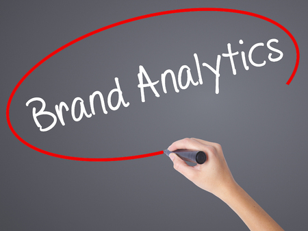 brand monitoring: Woman Hand Writing Brand Analytics with black marker on visual screen. Isolated on grey. Business concept. Stock Photo