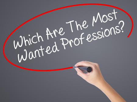 most talent: Woman Hand Writing Which Are The Most Wanted Professions? with black marker on visual screen. Isolated on grey. Business concept. Stock Photo