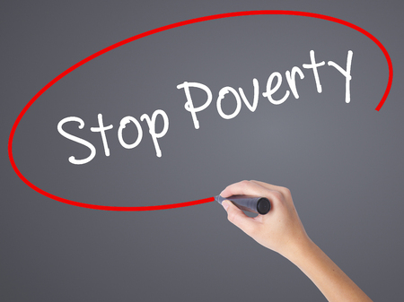 eradication: Woman Hand Writing Stop Poverty  with black marker on visual screen. Isolated on grey. Business concept. Stock Photo