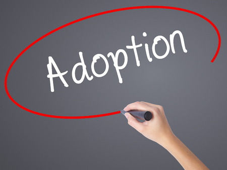 foster parenting: Woman Hand Writing Adoption with black marker on visual screen. Isolated on grey. Business, technology, internet concept.