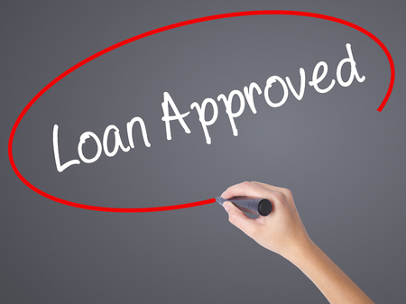 borrowing: Woman Hand Writing Loan Approved with black marker on visual screen. Isolated on grey. Business concept. Stock Photo