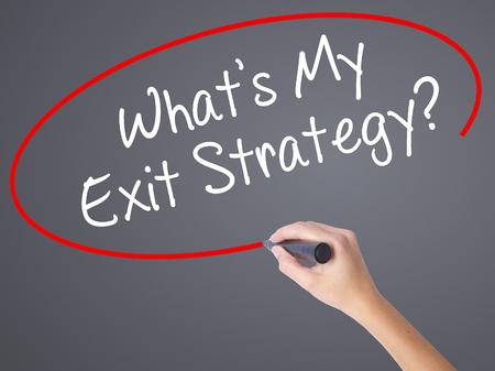 exiting: Woman Hand Writing Whats My Exit Strategy? with black marker on visual screen. Isolated on grey. Business concept. Stock Photo