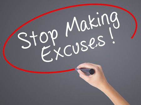 procrastination: Woman Hand Writing Stop Making Excuses with black marker on visual screen. Isolated on grey. Business concept. Stock Photo