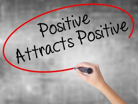 affirmation: Woman Hand Writing Positive Attracts Positive with black marker over transparent board. Isolated on grey. Business concept. Stock Photo