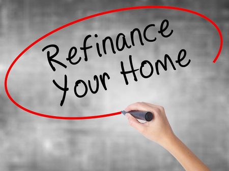 loaning: Woman Hand Writing Refinance Your Home with black marker over transparent board. Isolated on grey. Business concept. Stock Photo