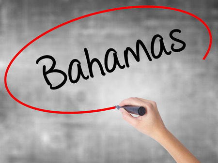 Woman Hand Writing Bahamas with black marker over transparent board. Isolated on grey. Business concept. Stock Photo