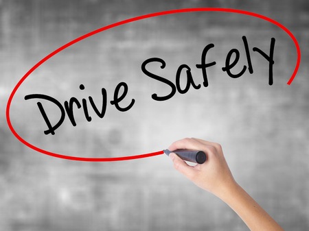Woman Hand Writing  Drive Safely with black marker over transparent board. Isolated on grey. Business concept. Stock Photo