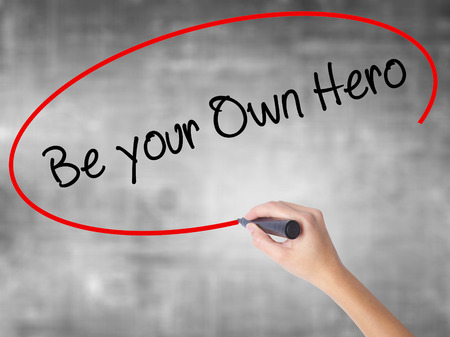 Woman Hand Writing  Be your Own Hero  with black marker over transparent board. Isolated on grey. Business concept. Stock Photo