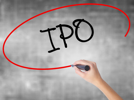 insider: Woman Hand Writing IPO (Initial Public Offering)   with black marker over transparent board. Isolated on grey. Business concept. Stock Photo Stock Photo