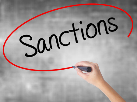 sanctioned: Woman Hand Writing Sanctions with black marker over transparent board. Isolated on grey. Business, technology, internet concept. Stock  Photo