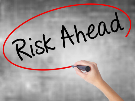 Woman Hand Writing Risk Ahead with black marker over transparent board. Isolated on grey. Business concept. Stock Photo