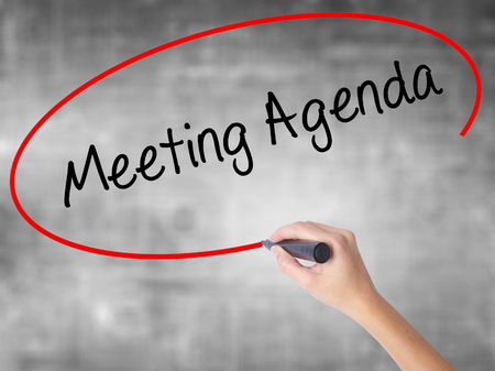 Woman Hand Writing Meeting Agenda  with black marker over transparent board. Isolated on grey. Business concept. Stock Photo Stock Photo