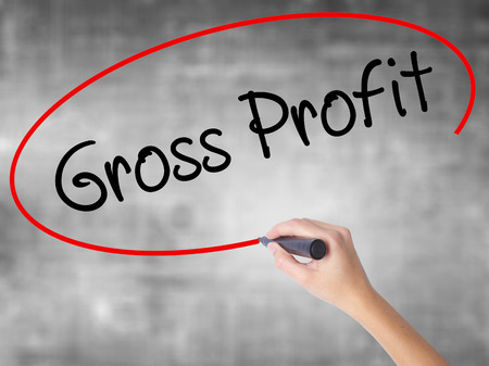 Woman Hand Writing Gross Profit with black marker over transparent board. Isolated on grey. Business concept. Stock Photo Stock Photo