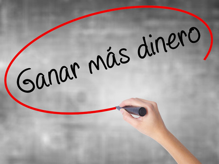 Woman Hand Writing  Ganar Mas Dinero  (Make More Money in Spanish)  with black marker over transparent board. Isolated on grey. Business concept. Stock Photo