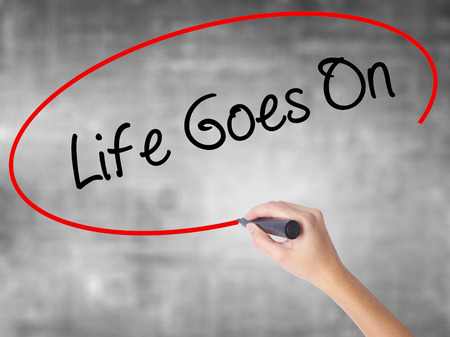 Woman Hand Writing Life Goes On with black marker over transparent board. Isolated on grey. Business concept. Stock Photo