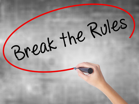 Woman Hand Writing Break the Rules with black marker over transparent board. Isolated on grey. Business concept. Stock Photo Stock Photo