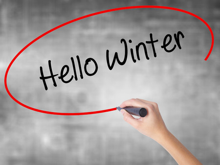 Woman Hand Writing Hello Winter with black marker over transparent board. Isolated on grey. Business concept. Stock Photo Stock Photo