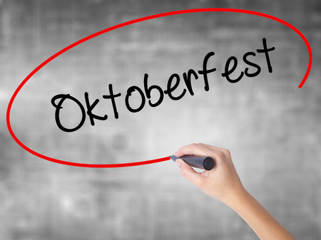 Woman Hand Writing Oktoberfest with black marker over transparent board. Isolated on grey. Business concept. Stock Photo