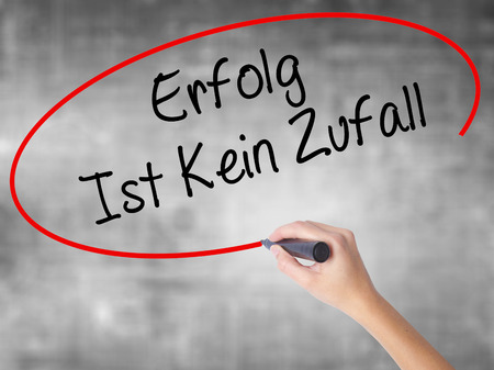 Woman Hand Writing Erfolg Ist Kein Zaufall (Success Is No Accident in German) with black marker over transparent board. Isolated on grey. Business concept. Stock Photo Stock Photo