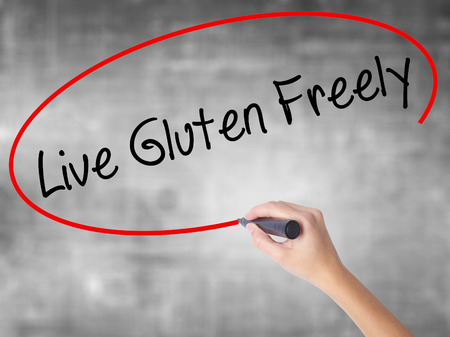 free education: Woman Hand Writing Live Gluten Freely with black marker over transparent board. Isolated on grey. Business concept. Stock Photo