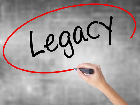 descendants: Woman Hand Writing Legacy with black marker over transparent board. Isolated on grey. Business concept. Stock Photo