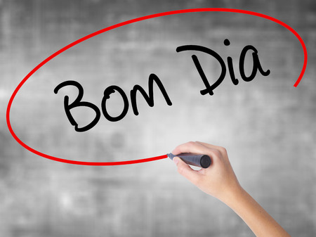 "Woman Hand Writing ""Bom Dia"" (In portuguese - Good Morning)  with black marker over transparent board. Isolated on grey. Business concept. Stock Photo Stock Photo"