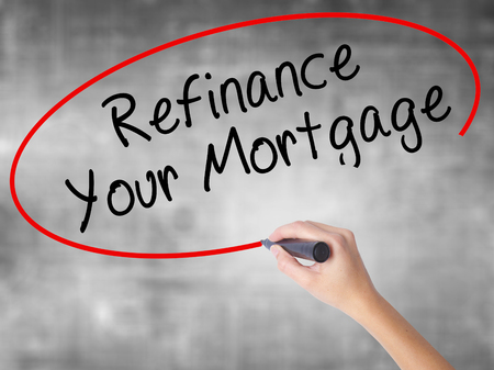 Woman Hand Writing Refinance Your Mortgage with black marker over transparent board. Isolated on grey. Business concept. Stock Photo Stock Photo