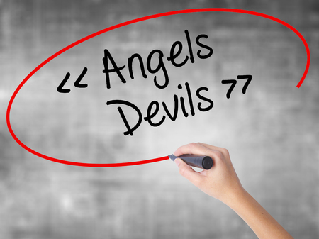 Woman Hand Writing Angels - Devils with black marker over transparent board. Isolated on grey. Business concept. Stock Photo Stock Photo