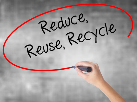 reduce reutiliza recicla: Woman Hand Writing Reduce Reuse Recycle with black marker over transparent board. Isolated on grey. Business concept. Stock Photo