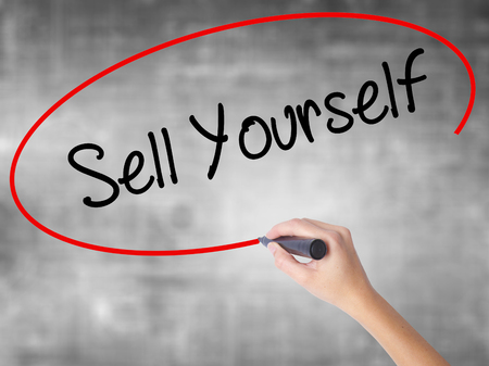 inteligent: Woman Hand Writing Sell Yourself with black marker over transparent board. Isolated on grey. Business concept. Stock Photo