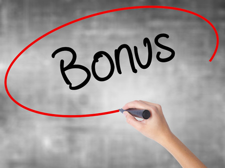 Woman Hand Writing Bonus with black marker over transparent board. Isolated on grey. Business concept. Stock Photo