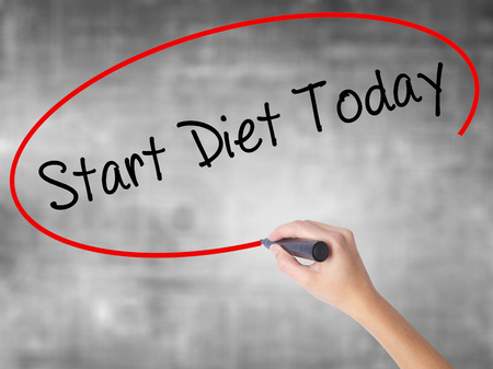 Woman Hand Writing Start Diet Today  with black marker over transparent board. Isolated on grey. Business concept. Stock Photo