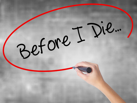 Woman Hand Writing Before I Die... with black marker over transparent board. Isolated on grey. Business concept. Stock Photo Stock Photo