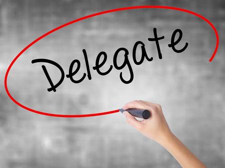 delegar: Mujer escritura de la mano Delegado con marcador negro sobre un tablero transparente. Aislado en gris. Concepto de negocio. Foto de stock
