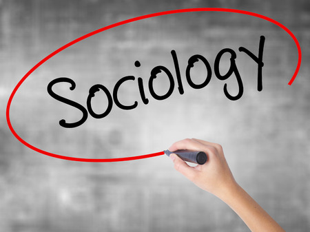 sociologia: Woman Hand Writing Sociology  with black marker over transparent board. Isolated on grey. Business concept. Stock Photo Foto de archivo