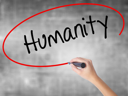 Woman Hand Writing Humanity  with black marker over transparent board. Isolated on grey. Business concept. Stock Photo