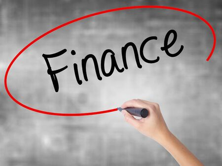 interst: Woman Hand Writing Finance with black marker over transparent board. Isolated on grey. Business concept. Stock Photo