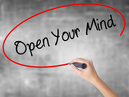 Woman Hand Writing Open Your Mind with black marker over transparent board. Isolated on grey. Business concept. Stock Photo Stock Photo