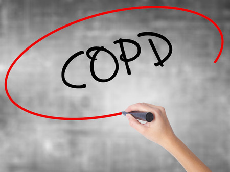 Woman Hand Writing COPD with black marker over transparent board. Isolated on grey. Business concept. Stock Photo Stock Photo