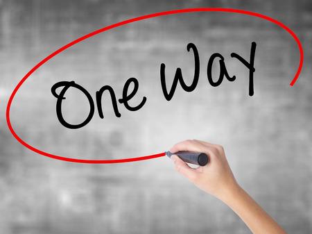 Mano de mujer escribiendo One Way con marcador negro sobre tablero transparente. Aislado en gris Negocios, tecnología, concepto de internet. Foto de stock