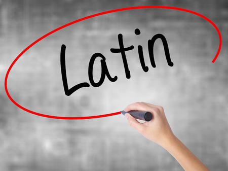 transnational: Woman Hand Writing Latin with black marker over transparent board. Isolated on grey. Business concept. Stock Photo