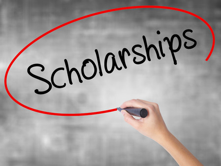 Woman Hand Writing Scholarships with black marker over transparent board. Isolated on grey. Business concept. Stock Photo