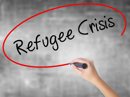 Woman Hand Writing Refugee Crisis with black marker over transparent board. Isolated on grey. Business concept. Stock Photo