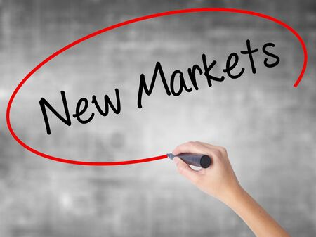 emerging markets: Woman Hand Writing New Markets with black marker over transparent board. Isolated on grey. Business concept. Stock Photo