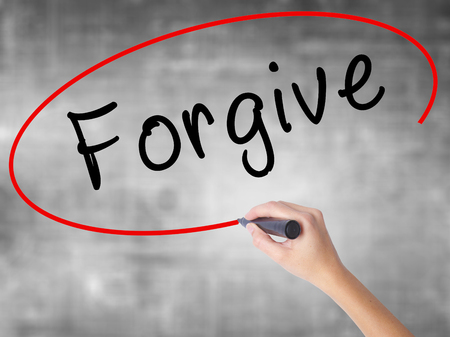 redeeming: Man Hand writing Forgive with black marker on visual screen. Isolated on white. Business, technology, internet concept. Stock Image Stock Photo