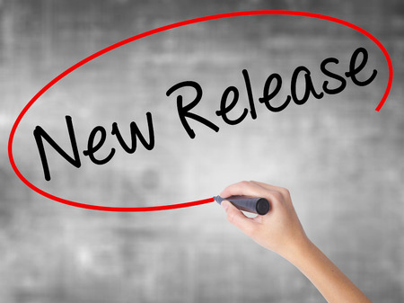 Mano de mujer escribiendo nuevo lanzamiento con marcador negro sobre tablero transparente. Aislado en gris Concepto de negocio. Foto de stock Foto de archivo - 70692799