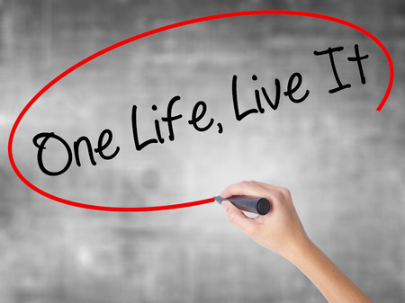 Woman Hand Writing One Life Live It with black marker over transparent board. Isolated on grey. Business concept. Stock Photo