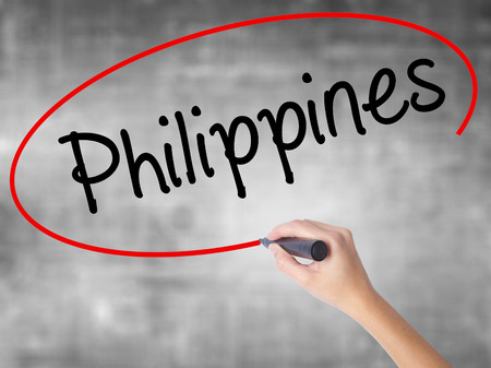 Woman Hand Writing Philippines with black marker over transparent board. Isolated on grey. Business concept. Stock Photo Stock Photo